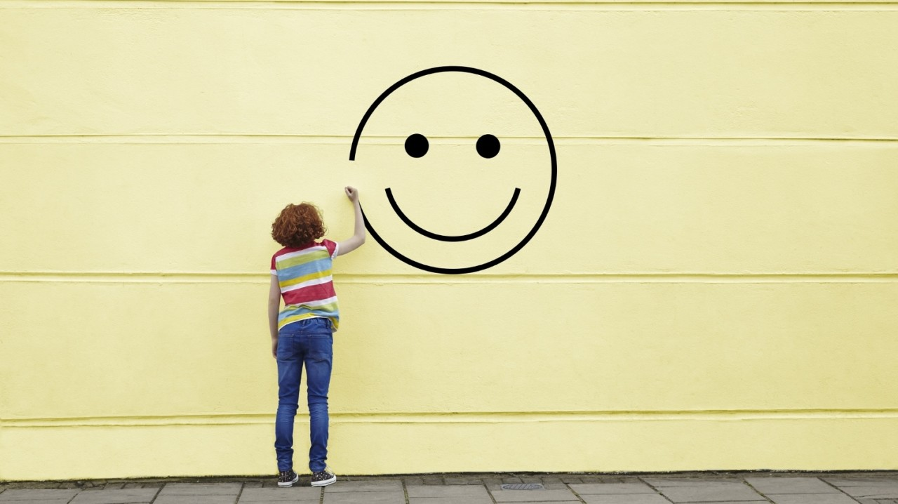Girl drawing smiley face on to a wall